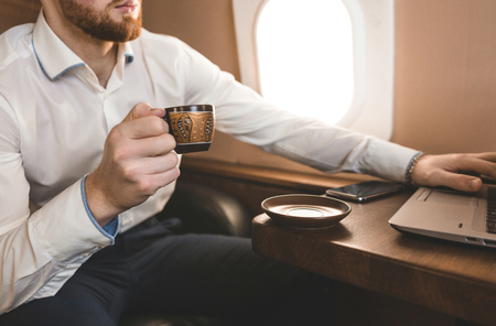 Attractive and successful businessman drinking coffee and working behind a laptop while sitting in a chair of his private jet.