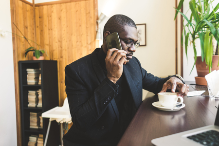 Young handsome dark-skinned businessman in a cafe talking on a cell phone with a cup of tea.
