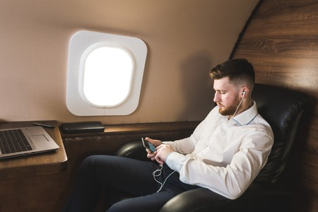 Young attractive and successful businessman is resting and listening to music works while sitting in the chair of his private business plane Reklamní fotografie