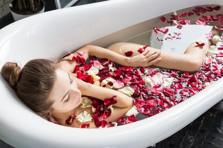 A young attractive girl takes a bathroom with flower petals and relaxes against the background of a beautiful light interior. Spa treatments for beauty and health with skin care