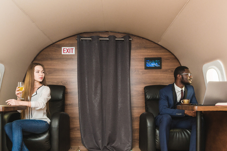 Young successful African-American businessman with glasses and an attractive female workmate blonde in a private jet. Service and flight first class