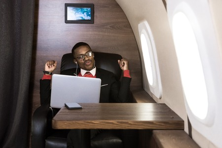 Attraktiver und erfolgreicher afroamerikanischer Geschäftsmann mit Brille, der an einem Laptop arbeitet, während er auf dem Stuhl seines Privatjets sitzt Standard-Bild