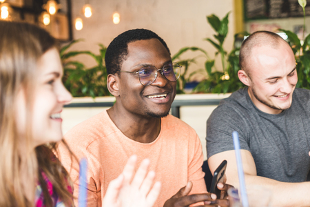 Meet young attractive people in the cafe. Friends chat, have fun, drink cocktails and eat