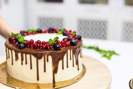 Confectioner decorates with berries a biscuit cake with white cream and chocolate. Cake stands on a wooden stand on a white table. The concept of homemade pastry, cooking cakes. 版權商用圖片
