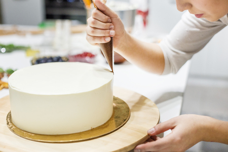 A confectioner squeezes liquid chocolate from a pastry bag onto a white cream biscuit cake on a wooden stand. The concept of homemade pastry, cooking cakes. Stock Photo