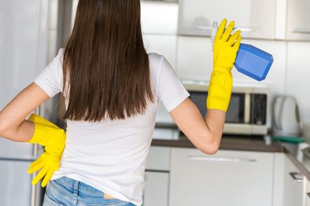 A young woman from a professional cleaning company cleans up at home. A man washes the kitchen in yellow gloves with cleaning supplies stuff.