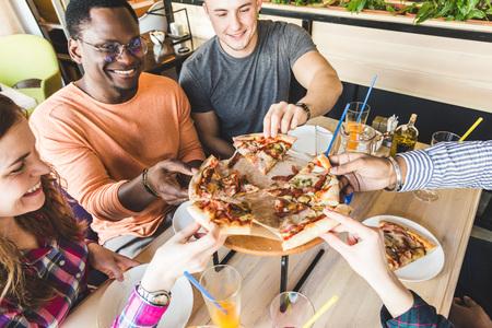 Eine Gesellschaft multikultureller junger Leute in einem Café, die Pizza essen, Cocktails trinken, Spaß haben