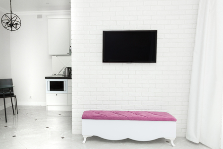 Apartment interior in modern light style. TV on the wall and a bench with a color accent. Stockfoto