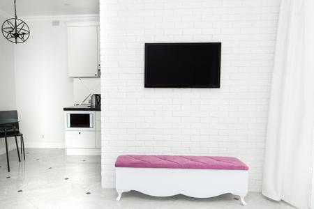 Interior del apartamento en estilo moderno y ligero. TV en la pared y un banco con acento de color. Foto de archivo