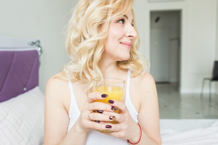 Attractive blonde woman sits on the edge of the bed at home and holds a stocker with orange juice in her hand. Morning mood and vigor