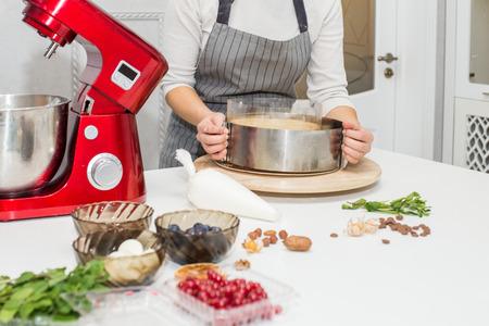 Il giovane pasticcere femminile monta la panna in una ciotola di metallo in un miscelatore elettrico rosso. Il concetto di pasticceria fatta in casa, cucina.