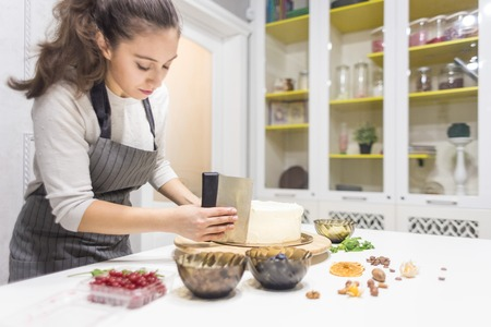 Konditor glättet weiße Sahne auf einem Kekskuchen mit einem Kochspatel. Das Konzept von hausgemachtem Gebäck, Kuchen kochen.