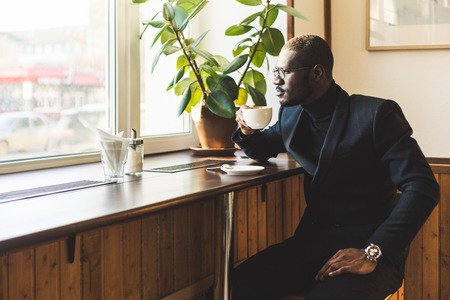 Young handsome dark-skinned businessman drinks coffee in a cafe. Фото со стока