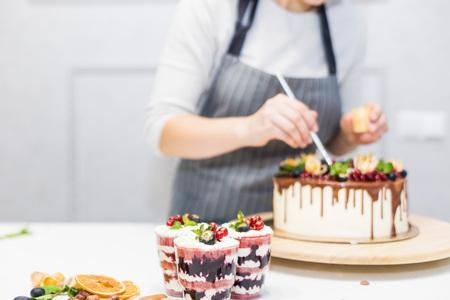 Decoración del postre terminado. El chef de repostería rocía dulces con polvo amarillo. El concepto de repostería casera, tartas de cocina. Foto de archivo