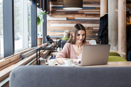 Attractive young woman sits at a table in a cafe with a cup of coffee and enjoys a laptop