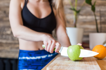 Attractive girl in sportswear preparing a healthy breakfast in the kitchen before training, cutting fruit and making fresh juice. Healthy lifestyle, fitness and beaut