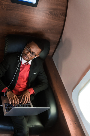 Attractive and successful African American businessman with glasses working on a laptop while sitting in the chair of his private jet Imagens