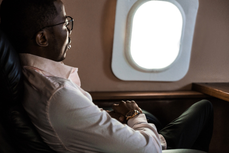 Successful young Afro American black businessman sitting in the chair of his private jet Imagens