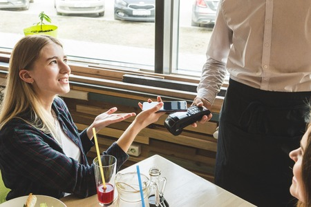Young attractive woman paying in cafe with contactless smartphone payment