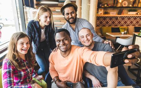 Groep jonge vrolijke vrienden zitten in een café, eten, drinken en drinken. Vrienden nemen selfies en nemen foto's.