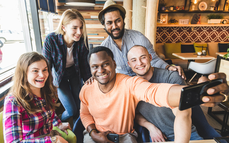 Grupa młodych wesołych przyjaciół siedzi w kawiarni, jedząc, pijąc napoje. Przyjaciele robią sobie selfie i robią zdjęcia.