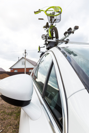 Bicycle transport - a childrens bicycle on the roof of a car against the sky in a special mount for cycling. The decision to transport large loads and travel by car 免版税图像