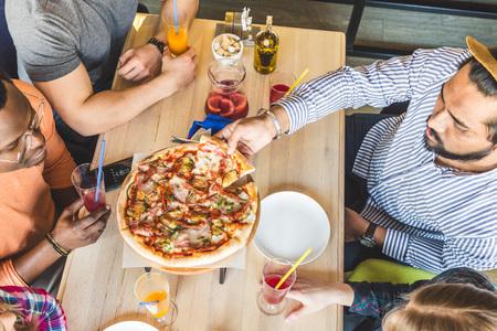 Een gezelschap van multiculturele jongeren in een café pizza eten, cocktails drinken, plezier maken