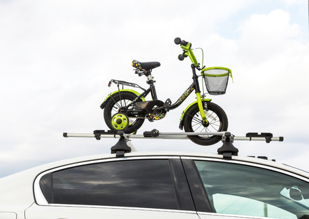 Bicycle transportation - a childrens bicycle on the roof of a car against the sky in a special mount for cycling. The decision to transport large loads and travel by car