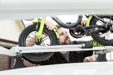 Bicycle transportation - A man fastens and installs a childrens bicycle on the roof of a car in a special mount for bicycle transport. The decision to transport large loads and travel by car.