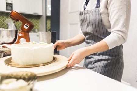 Confectioner smooths white cream on a biscuit cake with a cooking spatula. The concept of homemade pastry, cooking cakes Stock Photo