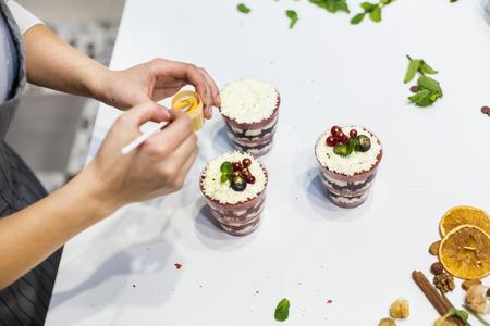 Decoración del postre terminado. El chef de repostería rocía dulces con polvo amarillo. El concepto de pastelería casera, tartas de cocina.