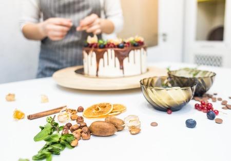 Pastelero decora con frutos rojos un bizcocho de galleta con crema blanca y chocolate. Cake se encuentra en un soporte de madera sobre una mesa blanca. El concepto de pastelería casera, tartas de cocina. Foto de archivo
