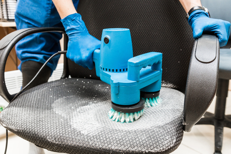Young man in workwear and rubber gloves cleans the office chair with professional equipment.