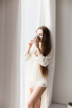 Attractive young girl in nightwear stands at the window and drinks coffee. Morning mood