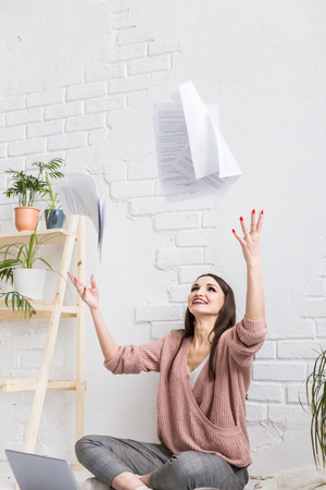 A young happy woman throws up a bunch of pieces of paper and documents sitting near the laptop, the freelance girl is happy and in a good mood. excitement and inspiration