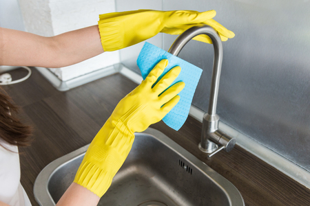 A young woman in yellow gloves washes crane with a sponge in the sink. House professional cleaning service.