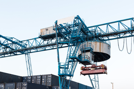 Large industrial port crane unloads cargo containers