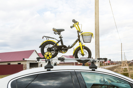 Bicycle transport - a childrens bicycle on the roof of a car against the sky in a special mount for cycling. The decision to transport large loads and travel by car Archivio Fotografico