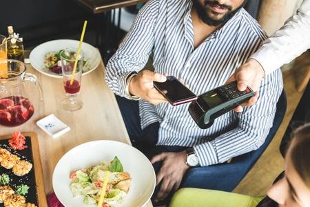 Jonge aantrekkelijke hindoe-man die in café betaalt met contactloze smartphonebetaling