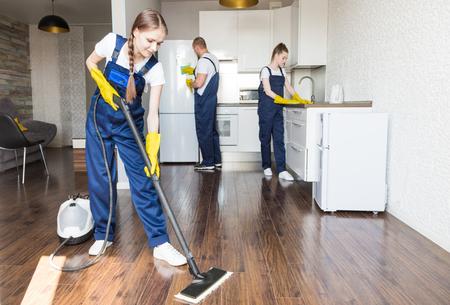 Servizio di pulizia con attrezzatura professionale durante il lavoro. pulizia professionale angolo cottura, lavaggio a secco divani, lavaggio vetri e pavimenti. uomo e donna in divisa, tuta e guanti di gomma Archivio Fotografico