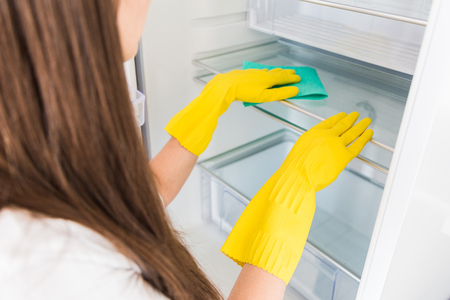 A young woman from a professional cleaning company cleans up at home. A man washes the kitchen washes the fridge in yellow gloves with cleaning supplies stuff.