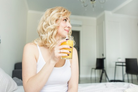 Atractiva mujer rubia sentada en el borde de la cama en su casa y sostiene un calcetín con jugo de naranja en la mano. Estado de ánimo y vigor matutinos