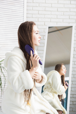 Attractive young girl in a white bathrobe combing hair standing in front of the mirror in the interior of the bathroom and doing morning procedures. Beauty and body care