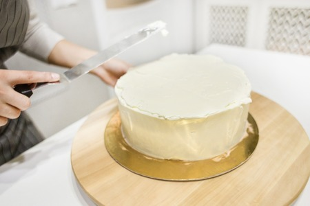 Confectioner smooths white cream on a biscuit cake with a cooking spatula. The concept of homemade pastry, cooking cakes