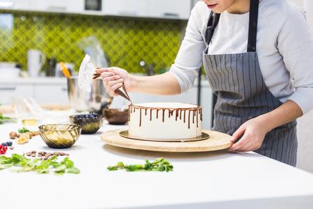 Een banketbakker perst vloeibare chocolade uit een spuitzak op een witte roombiscuitcake op een houten standaard. Het concept van zelfgemaakt gebak, taarten koken