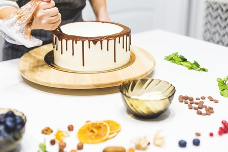 A confectioner squeezes liquid chocolate from a pastry bag onto a white cream biscuit cake on a wooden stand. The concept of homemade pastry, cooking cakes Standard-Bild