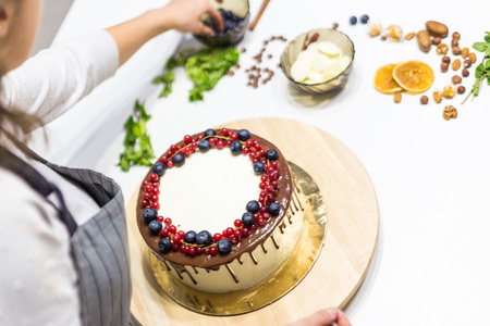 Confectioner decorates with berries a biscuit cake with white cream and chocolate. Cake stands on a wooden stand on a white table. The concept of homemade pastry, cooking cakes