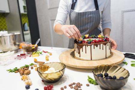 Konditor verziert mit Beeren einen Kekskuchen mit weißer Sahne und Schokolade. Kuchen steht auf einem Holzständer auf einem weißen Tisch. Das Konzept von hausgemachtem Gebäck, Kuchen kochen cooking