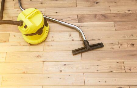 professinal cleaning. yellow vacuum cleaner on wooden floor. Stock fotó