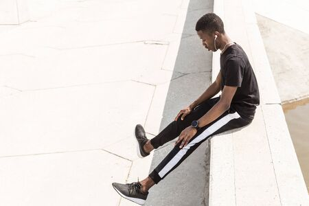 Athletic young afroamerican runner doing warm up on the promenade. Black Male running on outdoors. Healthy lifestyle concept. 스톡 콘텐츠